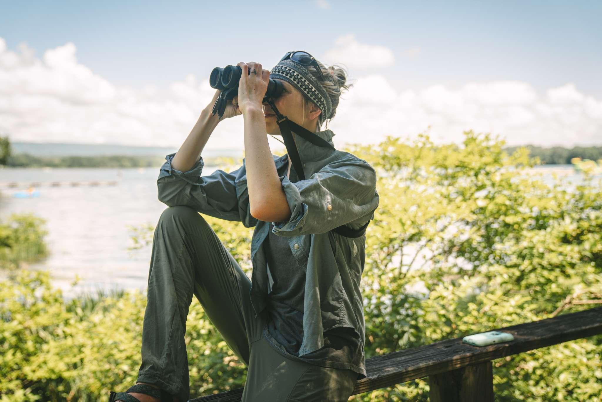 Laura Marsh, founder of Nova Conservation doing wildlife conservation work by looking through binoculars